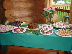 A table featuring platters of various desserts, pastries, and cakes is set up in the dining room of the lodge