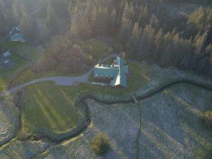 High above aerial drone shot of Bear Track Inn at dusk