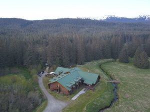 Aerial shot of Bear Track Inn with rolling forests and mountains in the distance