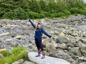 Teenager triumphantly poses on a rock on the Alaskan shoreline