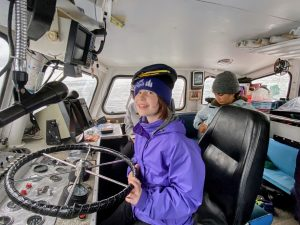 Child holds the steering wheel of a boat off the Alaskan shoreline