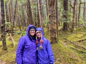 Mother and daughter posing in a moss-covered forest in Alaska
