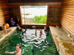 Group enjoying an indoor pool with view of the coastline at the Bear Track Inn