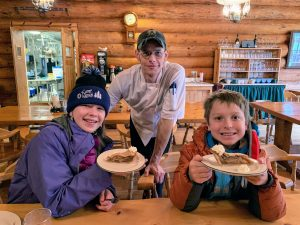 Family showing off beautiful slices of pie in the Bear Track's dining room with a little peek into the industrial kitchen in the background