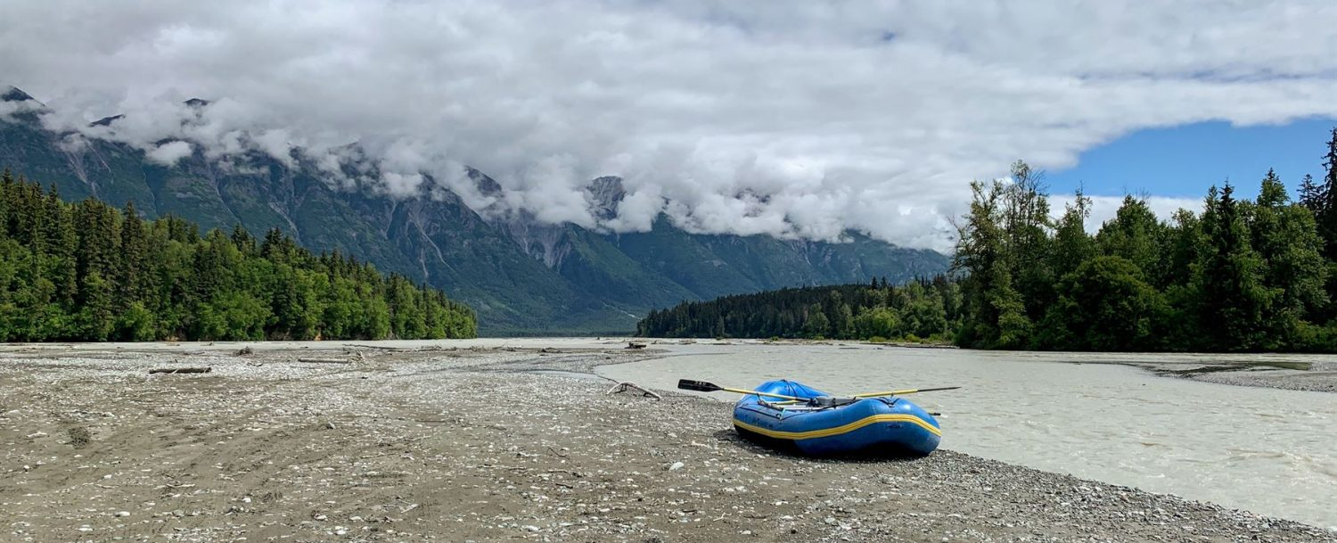 Dingy sitting beside a riverbed with forests and mountains in the distance