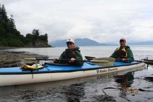 Kory and David in a dual-kayak just by the shore