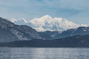 Beautiful blue mountains leading up to snow-capped peaks across a lake in Alaska