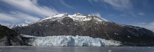 View from the water of glacier and snowdrifted mountains in this distance