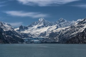 Long shot of a large glacier and the massive snow-capped peaked mountains surrounding it