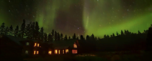The sky is lit green with the northern lights above the lodge