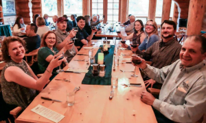 A group of men and women sit at a long table in the lodge's dining room holding up glasses of wine and smiling at the camera