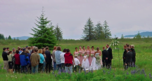 A wedding ceremony takes place in a large grassy meadow on the property of the lodge. The bridal party stands up front featuring bridesmaids in pink dresses, a flower girl, the bride, the groom, the officiant, and groomsmen in black suits. A large audience stands and watches.