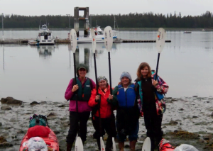 A group of four women in thermal clothes each hold a single kayak paddle upright while standing on a beach. A large lake with several fishing boats is behind them
