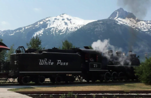 A black train with steam emerging above the locomotive is photographed on a railroad in front of a snow covered mountain range