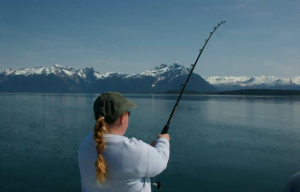 A woman with her back turned to the camera holds a fishing rod cast into the ocean with a view of snow covered mountains in the background