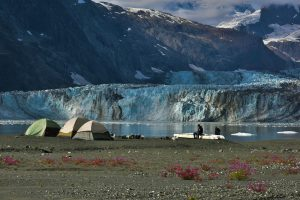 Campers on an Alaskan shoreline with view of glacier