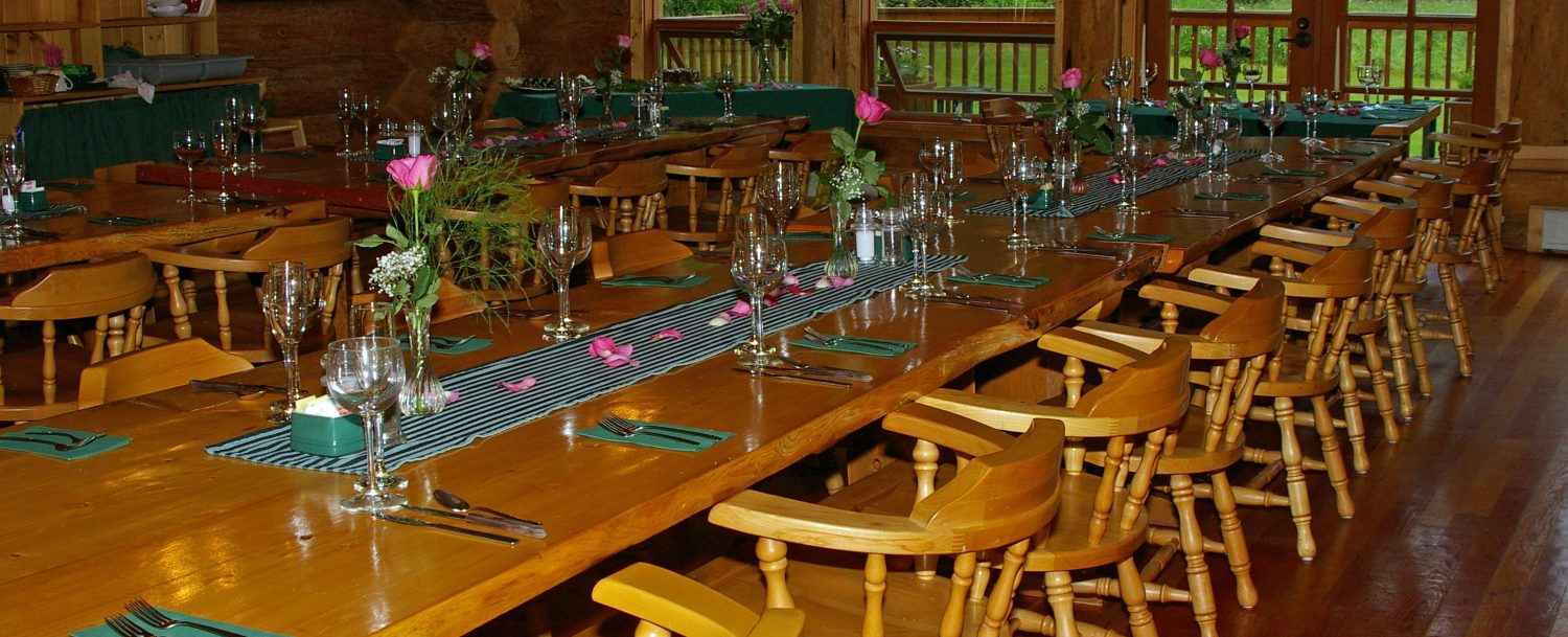 A dining room table in the lodge is set up for a formal dinner and decorated with pink flowers in glass vases, empty wine glasses, and green linens
