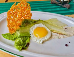 Two romaine lettuce leaves with a fried egg on top and a parmesan crisp on a bed of ceaser dressing